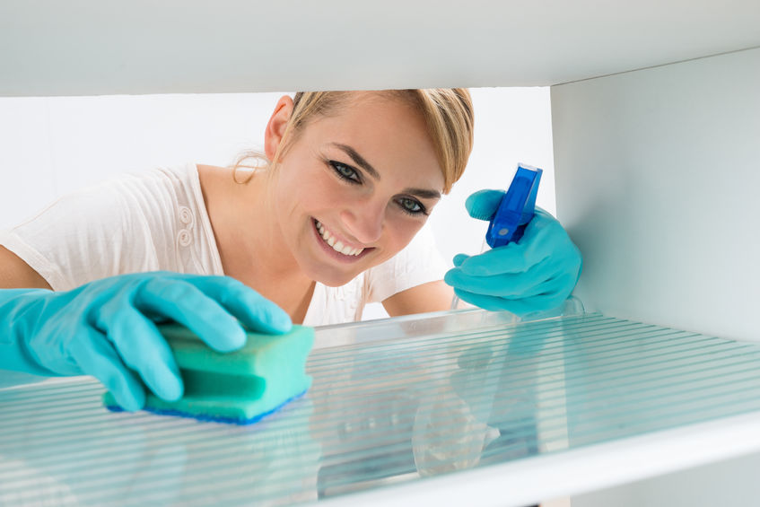 Maid in America cleaning the refrigerator - a service we offer