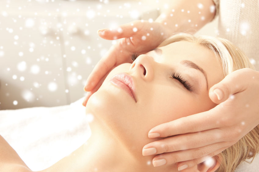 beauty, health, holidays, people and spa concept - beautiful woman in spa salon getting face or head massage